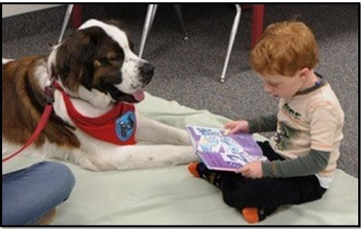 A young boy reading with a service dog