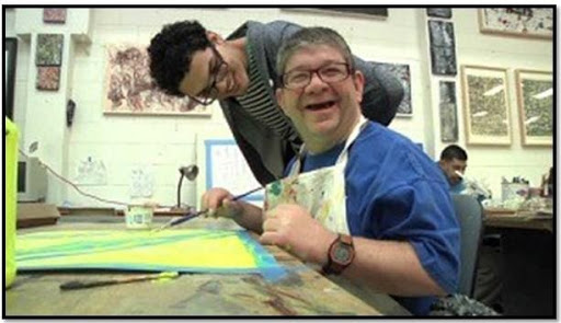 A man smiling while he paints